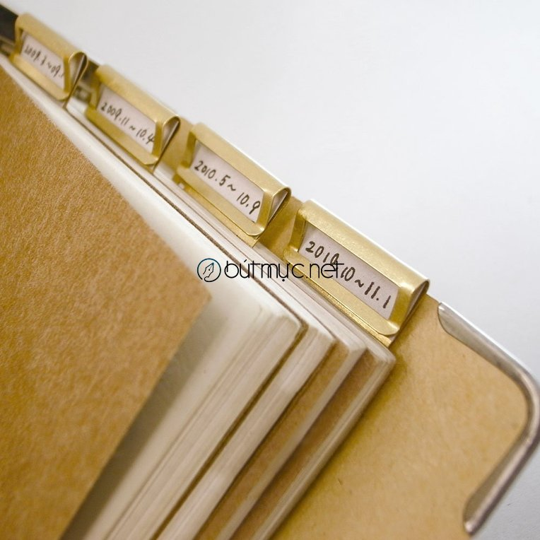 Kẹp giấy bằng đồng có khoang cho bạn chèn thêm mẫu giấy nhỏ để ghi thêm tựa đề hay ngày tháng.